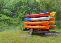kayaks by car delivered to the river, on the trailer with eight canoes