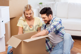 happy couple unpacking boxes at new home