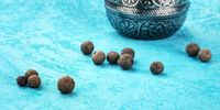 A panorama of allspice, Jamaican pepper. Black peppercorns with a vintage pepper mill, close-up on a vibrant blue background