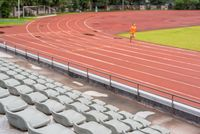 Selective focus on seats in a stadium with a man running