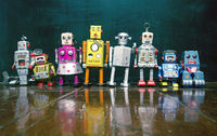 a line of vintage robots and a blackboard