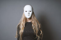 mysterious woman hiding face and identity behind mask