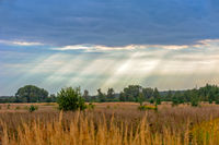 Rural landscape and sun rays through clouds