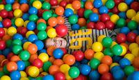 boy having fun in pool with colorful balls