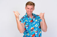 Happy young tourist man with blond hair giving thumbs up and looking excited