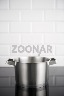 Stainless steel pot on the induction stove with white metro tiles in the background