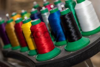 Garn in kräftigen Farben auf Nähspulen angeordnet - Nahaufnahme Nähseide