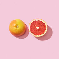 Two halves of a ripe grapefruit on a pink background with reflection of the shadow and space for text. Vitamin healthy food. Top view