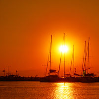 Silhouettes of yachts with tall masts at sunset
