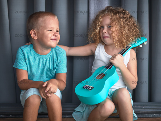 Portrait of a cute kids with ukulele