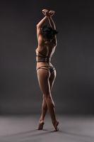 Slim brunette in bdsm style lingerie rearview