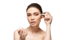girl applying eye serum isolated on white