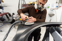 Car mechanic with dust mask grinds a car part in a service station - Serie car repair workshop