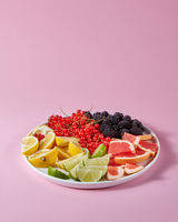 Set of different citrus fruits and berries in a plate presented on a pink background with copy space. Healthy Vitamin Food