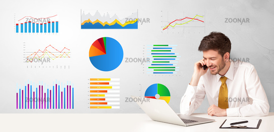 Businessman sitting at desk with reports and graphs