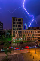 A spectacular lightning over an office bulding in a city at night.