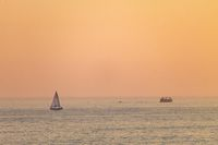 Distant Sailboat at Sunset