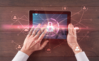 Hand using tablet with network security and online storage system concept