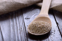 Raw organic superfood gluten free quinoa seeds in wooden spoon on kitchen table closeup