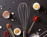 Metal whisk, spoon with red pepper knife and halved boiled eggs on a black concrete background. Cooking Concept. Flat lay