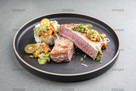 Traditional exotically tuna fish fillet with mango salsa and rice as closeup on a modern design black plate