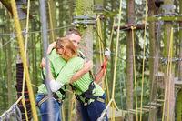 Junges Paar umarmt sich glücklich im Kletterwald