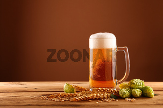 Close up beer glass, hops and barley over brown