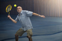 Senior plays tennis indoor.
