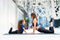 Young adult mom and little daughter together on aerobics