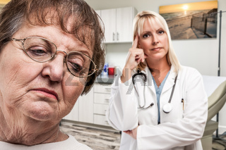Empathetic Doctor Standing Behind Troubled Senior Adult Woman In Office