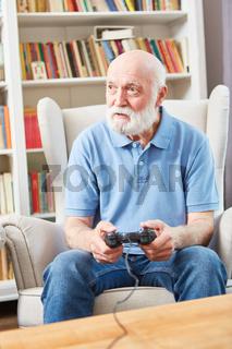 Senior Mann spielt Videospiel mit Konsole