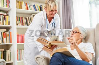 Ärztin und Seniorin recherchieren in einem Buch