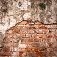 Old brick wall in a background image. Plastered Brickwall With Chipped Stucco Pieces. Red Textured Brick Wall With Damage Surface. Old Grunge Abstract Background