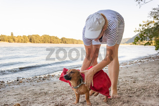 Woman drying her small mixed breed dog at the river beach with a towel. Dog, lifestyle and summer vacation concept.