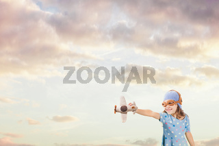 Girl in an old style knitted pilot helmet holding toy airplane