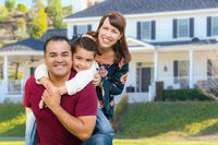 Happy Mixed Race Family Portrait In Front of Their House