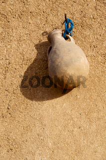 in a old straw wall a hanging vase