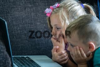 Little children watching cartoons on a laptop
