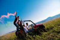 group of young people having fun while driving a off road buggy car