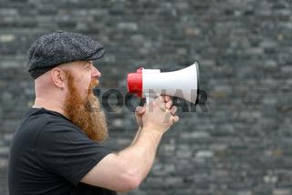 Big man yelling into a megaphone