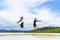 Two asian teen girls friends jumping enjoy on the beach