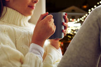 close up of girl with tea mug sitting at window