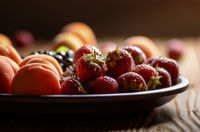 Ripe organic blueberries apricots and strawberries in clay plate on wooden table