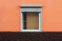 One window in the house is half closed by external shutters. bright orange and brown color of the plaster