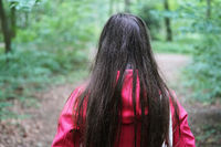 rear view of unrecognizable young woman during a walk in the woods