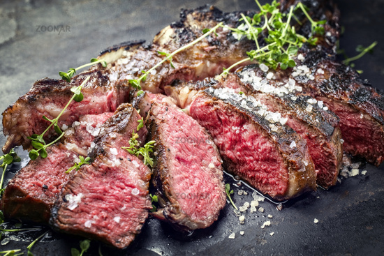 Traditional barbecue dry aged wagyu tomahawk steak sliced salt and herb as closeup on a rustic old black board