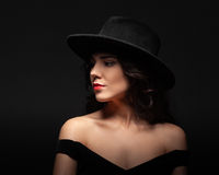 Profile portrait of a beautiful lady wearing a black hat