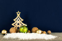 Christmas decoration dark background with wooden tree glass balls and snow