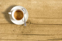 top view of a small cup of coffee on a wooden table