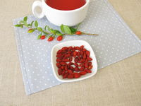 A cup of tea, fruit tea with dried goji berries